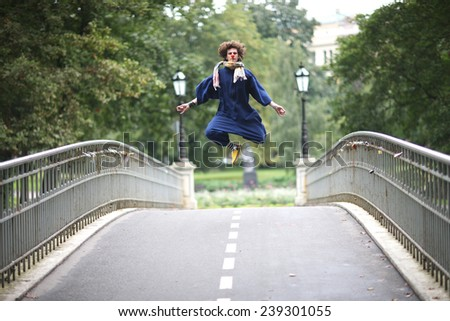 Clown jumping high in the city park - stock photo
