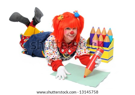 Clown laying down on the floor and writing with large color pencils - stock photo