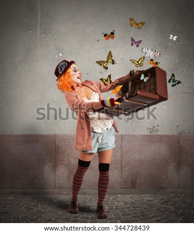 Clown opens a suitcase which emerges butterflies - stock photo