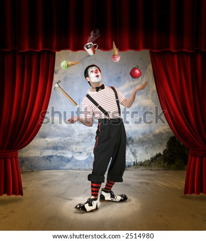 Clown performing on stage with red curtains - stock photo