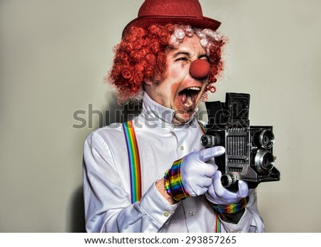 Clown photographer wearing a red hat and wig with a vintage camera on a white background - stock photo