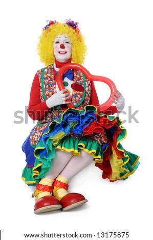 Clown sitting and holding a balloon heart - stock photo