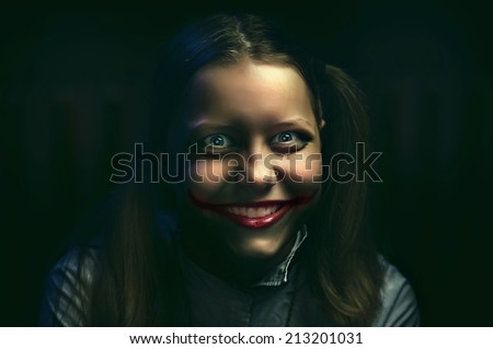 Clown teen girl with a sinister smile - stock photo