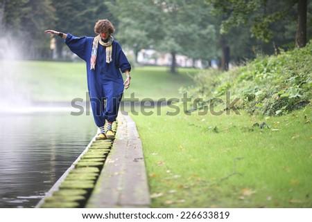 Clown walking along the river bank - stock photo