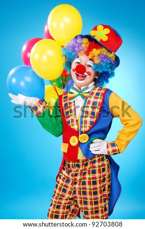 Clown with balloons over the blue background - stock photo