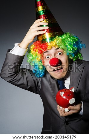 Clown with piggybank in funny concept - stock photo