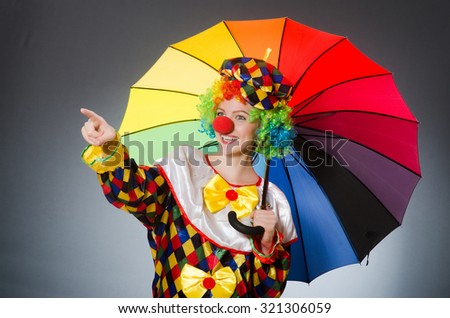 Clown with umbrella in funny concept - stock photo