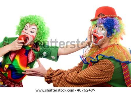Clowns are fighting for an apple. Isolated - stock photo
