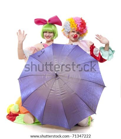 Clowns behind an umbrella wave hands at parting - stock photo