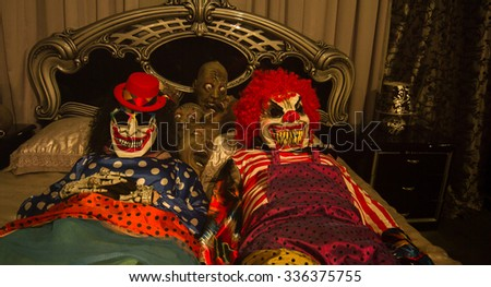 Clowns husband and wife lie in bed. Halloween.