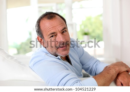 Clsoeup of handsome senior man relaxing in couch - stock photo