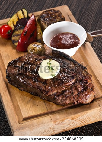 Club Beef steak with pepper sauce and Grilled vegetables on cutting board on dark background - stock photo