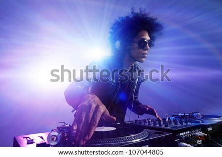 Club DJ with afro hairstyle playing mixing music on vinyl turntable at party wearing sunglasses with lens flare from nightlife lights. - stock photo