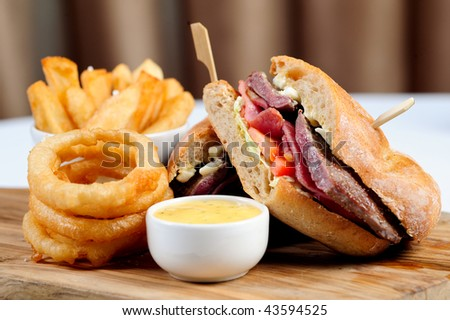 Club House Grill with onion rings, chips served on a wooden butchers block - stock photo