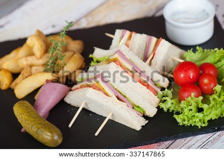 club sandwich with grilled chicken breast, baked potatoes, vegetables and egg