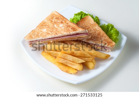 Club sandwich with ham and cheese in one dish with french fries - stock photo