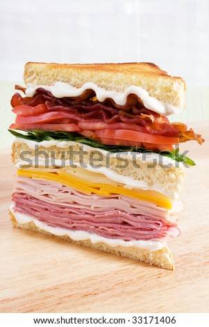 Club sandwich with ham, turkey, cheddar cheese, swiss cheese, lettuce, tomatoes, bacon, and mayonnaise.