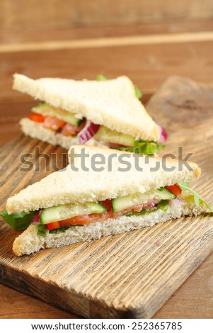 Club sandwich with salmon on wooden background
