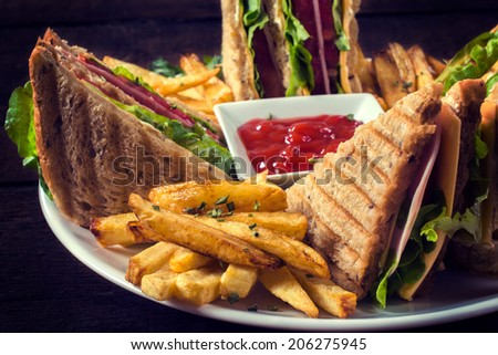 Club sandwiches and french fries in the plate. - stock photo