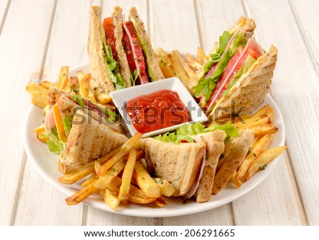 Club sandwiches and french fries in the plate on wooden background  - stock photo