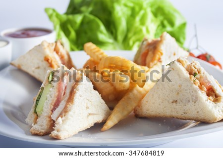 Club sandwiches with grilled chicken, tomato, lettuce, cheese, cucumber and dressing sauce, served on a white plate with french fries. - stock photo