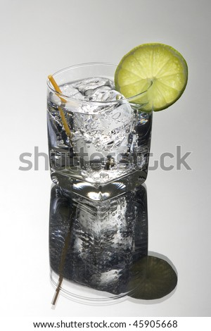 Club soda or Gin or Vodka and tonic mixed drink with lime slice garnish on a grey background - stock photo