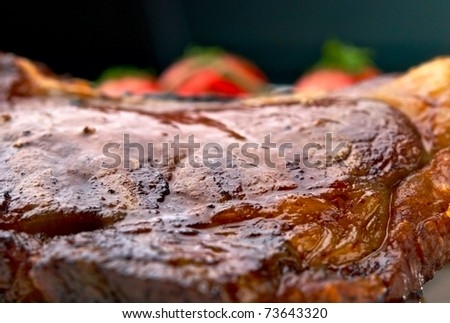 Club Steak. Veal on the bone. Macro of grilled meat ribs on white plate with cherry tomatoes and dark hot sauce - stock photo