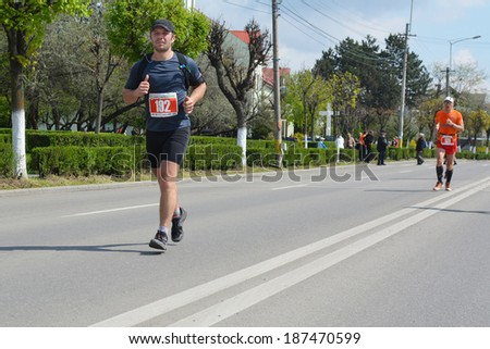 """CLUJ-NAPOCA, ROMANIA - APRIL 13, 2014: Unidentified marathon runners. Young woman and young man run on the streets of Cluj-Napoca at the """"AROBS"""" International Marathon. - stock photo"""
