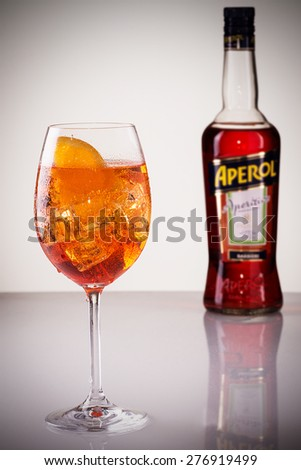 Cluj-Napoca, Romania, May, 11, 2015; Glass of light drink with bottle of Aperol, Aperitivo Poco Alcolico, Liqueur alc. 11%, 1L. Famous Italian aperitif. Produced by DCM S.P.A., Italy - stock photo