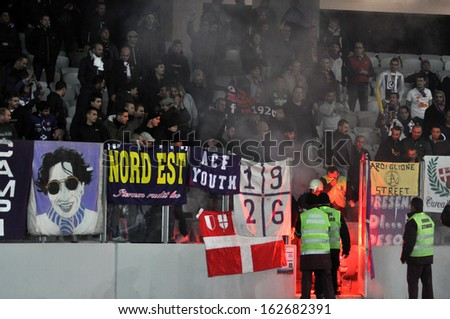 CLUJ - NOVEMBER 7: ACF FIORENTINA ultras hooligans burning flares, during an Europa League Group stage match against CS Pandurii Targu Jiu, final score 2:1. On Nov. 7, 2013 in Cluj Napoca, Romania - stock photo