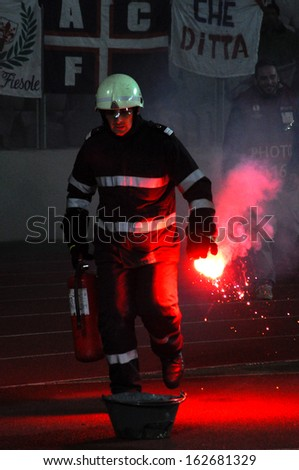 CLUJ - NOVEMBER 7: Fireman in action after ACF FIORENTINA ultras fans throwing a fire flare, during a match against CS Pandurii Targu Jiu, final score 2:1. On Nov. 7, 2013 in Cluj Napoca, Romania - stock photo