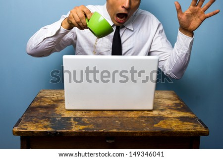 Clumsy businessman spilling coffee on his laptop computer - stock photo