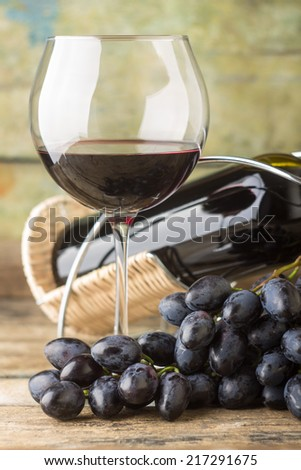 Cluster of fresh dark blue grapes with red wine in glass on wood background - stock photo