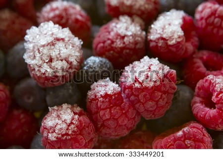 Cluster of Frozen Ice-Covered Raspberries and Blueberries - stock photo