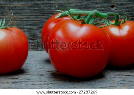 Cluster of red vine tomatoes on old barn wood planks - stock photo