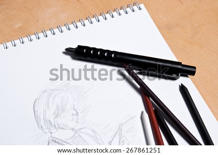 Clutch pencil with with notebook on the wooden background. Clutch pencil and different kinds of art materials: sanguine, graphite, crayons, charcoal over wooden background. - stock photo
