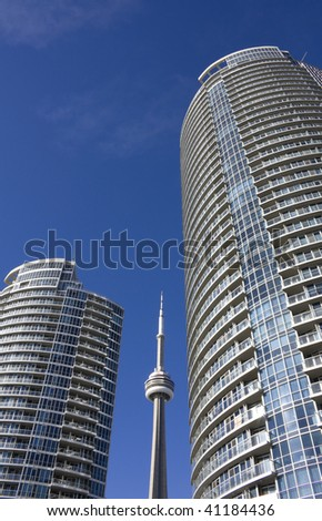 CN Tower beside condominium in toronto against clear blue sky - stock photo