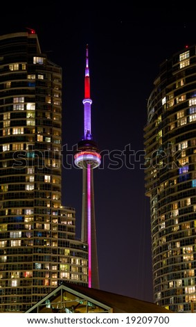 CN Tower between two condominiums at night - stock photo
