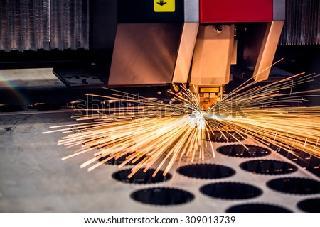 CNC Laser cutting of metal, modern industrial technology. Small depth of field. Warning - authentic shooting in challenging conditions. A little bit grain and maybe blurred. - stock photo