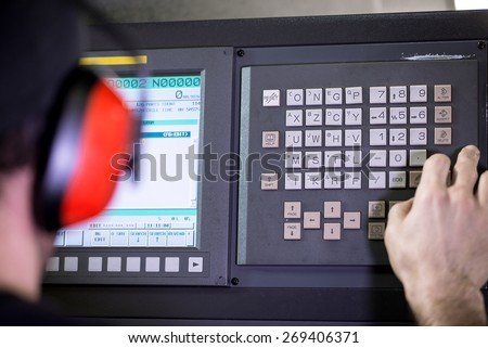 CNC operator, mechanical technician worker at metal machining milling center in tool workshop inserting data with keyboard wearing noise cancelling headset - stock photo