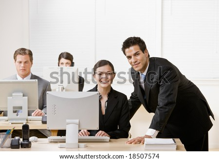 Co-worker listening to supervisor explain problem on computer - stock photo