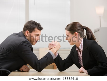Co-workers aggressively arm wrestling for dominance - stock photo