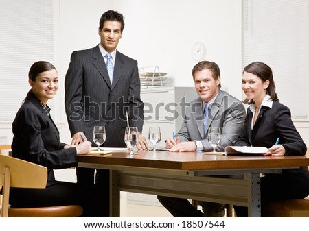 Co-workers and supervisor meeting in conference room - stock photo