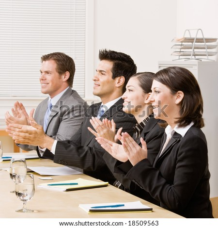 Co-workers applauding in meeting in conference room - stock photo