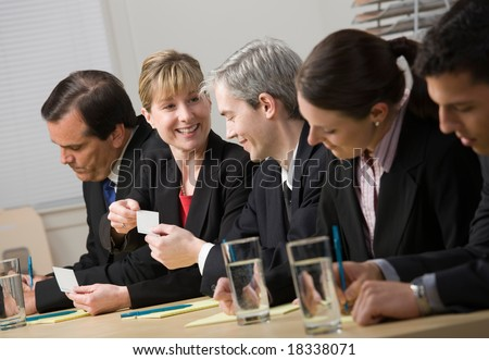 Co-workers exchanging business cards while sitting on panel - stock photo