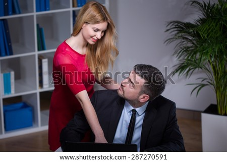 Co-workers flirting in the office during work - stock photo