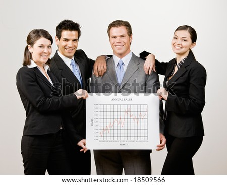 Co-workers holding financial line graph which analyzes the business? success - stock photo