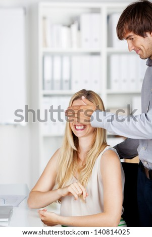 co-workers in the office holding hand on eyes - stock photo