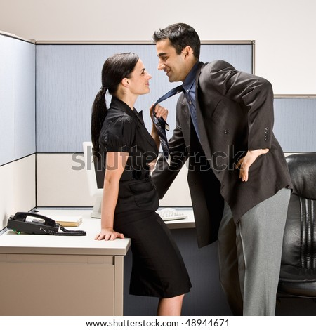 Co-workers kissing in office cubicle - stock photo