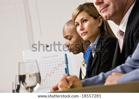 Co-workers listening during meeting in conference room - stock photo